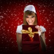 Portrait of a santa woman with a christmas gift on red background — Stock Photo