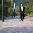 Businessman walking in a park — Stock Photo