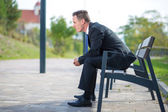 Businessman waiting on a bench in park — Stock Photo