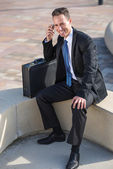 Businessman calling in park — Stock Photo