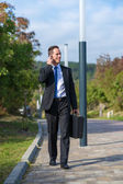 Businessman in park with phone — Stock Photo