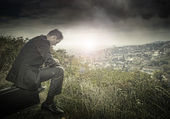 Lonely businessman on the hillside — Stock Photo