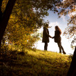 Lovers holding hands walking in the autumn park — Stock Photo