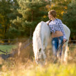 Woman with a white horse — Stock Photo