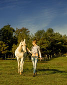 Woman walking on a white horse at the ranch — Stock Photo