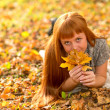 Woman in the autumn leaves — Stockfoto