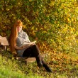 Woman read the book in autumn forest — Stock Photo