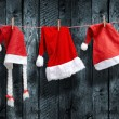 Three Santa Claus hat hanging on a clothesline — Stock Photo