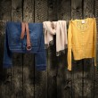 Women's clothing on a clothesline on wood background — Stock Photo