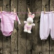 Baby girl clothes and bunny on a clothesline — Stock Photo