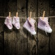 Baby girl shoes and socks on the clothesline — Stock Photo #35173955
