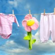 Baby girl clothes with flower on the clothesline — Stock Photo