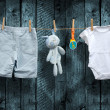 Baby boy clothes and stuffed bunny on a clothesline — Stock Photo