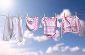Clean baby girl clothes on the outdoor clotheslin — Stock Photo