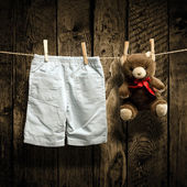 Baby clothes and a teddy bear on clothesline — Stock Photo