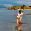 Beautiful little girl on the beach fishes — Stock Photo #38328741