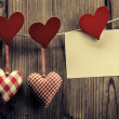Stock Photo: Valentine's Day wallpaper - Textile hearts hanging on the rope, message