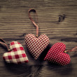 3 pieces of fabric hearts, polka dots , plaid, on wood background — Zdjęcie stockowe