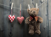 Valentine's Day wallpaper - Teddy Bear hanging with textile hearts — Stock Photo