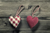 2 pieces of fabric hearts, polka dots , plaid, on wood background — Stock Photo
