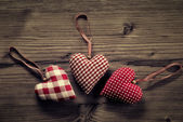 3 pieces of fabric hearts, polka dots , plaid, on wood background — Stock Photo