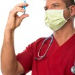 Handsome young doctor with mouth mask, stethoscope and syringe — Stock Photo
