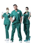 Doctor and two nurses in green dress, in mouth mask, with injections and stethoscope — Stock Photo