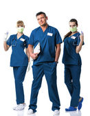 Doctor and two nurses in blue  dress, in mouth mask, with injections and stethoscope — Stock Photo