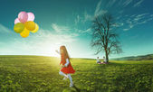 Happy girl running in a meadow with colorful balloons — Stock Photo