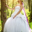 Beautiful bride relying on the tree — Stock Photo #45081243