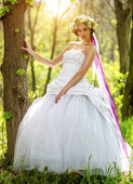 Beautiful bride relying on the tree — Stock Photo