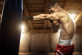 Young man boxing, exercise in the attic — Stok fotoğraf