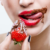 Red female lips with chocolate mouth, holding strawberries — Stok fotoğraf