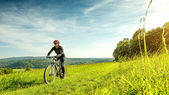 Sport bike woman in a beautiful meadow — 图库照片