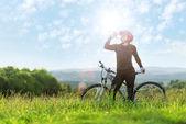 Sport bike woman drinking on a meadow — Stock fotografie