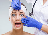 Beautiful woman face with surgical markings when startled look — Stock Photo