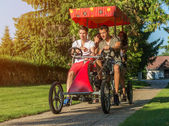 People in a four-wheeled bicycle — Photo