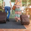 Young couple standing at hotel corridor upon arrival, looking for room, holding suitcases — Stock Photo #49691391