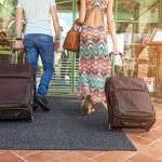 Młoda para w hotelu korytarz po przyjeździe, poszukuje pokoju, trzymając walizki — Zdjęcie stockowe #49691391