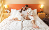 Young Couple lying in the bed of a hotel room — Stock Photo