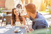Young couple talking on the terrace of the restaurant, while eating — Stock Photo