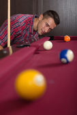 Young man playing billiard — 图库照片