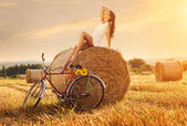 Woman sitting on bale of wheat — Stockfoto