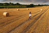 Woman cycling in wheat field — Stockfoto