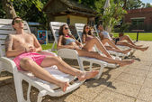 Four friends on sun loungers — Stock Photo