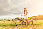 Woman with bike in field — Stok fotoğraf