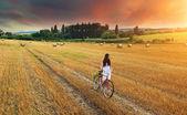 Woman pushes bike in field — Stock Photo