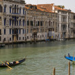 Gondolier with his gondola in the Grand Canal of Venice, Italy - Stock Photo