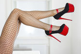 Legs of a woman wearing fishnet stockings and extreme red platfo — Stock Photo