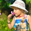 Little girl smells a flower in the garden — Stock Photo